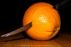 Old kitchen knife and orange. On black background stock photography