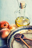 Old kitchen pan wooden spoon three onions carafe with olive oil on wooden table. Stock Images