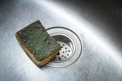 Dirty scrub sponge in a sink ,Old Kitchen Sponge Could Give Diar. Old Kitchen Sponge Could Give Diarrhea Stock Photos