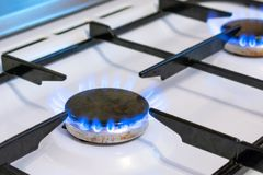 Old kitchen stove cook with blue flames burning. Possible leakage and gas poisoning. Household gas stove stock photo