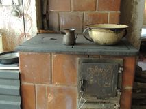 Old kitchen tools. On the tile stove in a country house stock photo