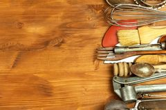 Old kitchen utensils on a wooden board. Sale of kitchen equipment. Chef`s tools. Old kitchen utensils on a wooden board. Sale of kitchen equipment. Chef`s tools stock image