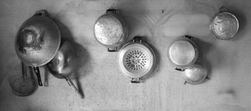 Old kitchenware hang on cement wall,black and white concept Stock Photo