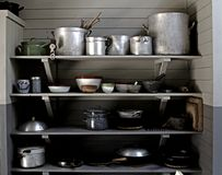 Old kitchenware pots and pans. Old kitchen shelves with pots and pans Stock Photos