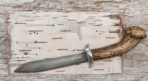 Old knife on the birch bark and weathered wood Royalty Free Stock Image