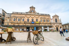 Old knife grinder bicycle and main square in Ostuni, Italy Royalty Free Stock Images