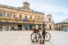 Old knife grinder bicycle and main square in Ostuni, Italy Royalty Free Stock Image