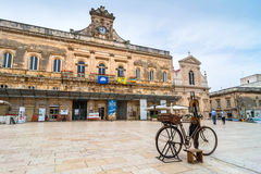 Old knife grinder bicycle and main square in Ostuni, Italy Royalty Free Stock Photos