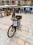 Old knife grinder bicycle and main square in Ostuni, Italy Royalty Free Stock Photography