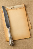 Old knife on yellowed blocknote Stock Image