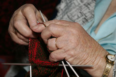 Old Knitting Hands. A pair of old hands knitting some red and black socks Royalty Free Stock Photos