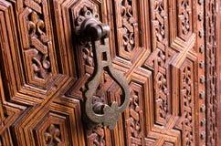 Old knocker in  wooden door. Old knocker in ornamental wooden door Royalty Free Stock Images