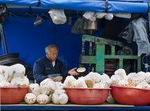 Old korean man making corn flat bread Stock Photos