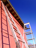 Old Ladders and Building. Two old ladders leaning against an old, red building Stock Images