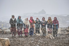 Old ladies in the middle of snow waiting animals to return from pasture. Areas of high Karakoram Mountains Pakistan. Upper Shimshal Royalty Free Stock Images