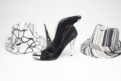 Old ladies shoe on high heels and and a hat. Black old ladies shoe on high heels with a hat on a white background royalty free stock images