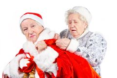 Old Ladies- Snow Maiden and Santa. Old Ladies. Snow Maiden helps Santa Clause to keep the bag with gifts royalty free stock images