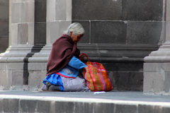 Old lady awaits for alms. A old woman awaits outside of a church for alms, in te meantime check in his plastic bag for food stock photography