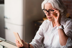 Old lady is being worried receiving new message on her phone Stock Images