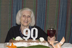 Old lady celebrating her 90th birthday. Grandma celebrating her 90th birthday with some red wine Stock Images