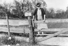 Free Old Lady Climbing Fence With Fishing Poles In Early 1900s Stock Photos - 141416623