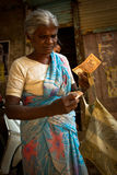 An old lady counts her money in the Dharavi Slums in Mumbai Indi Royalty Free Stock Photography