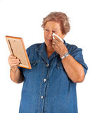 Old lady crying watching a blank photo frame Royalty Free Stock Image