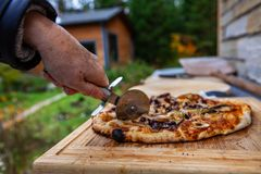 Old lady is cutting a pizza that just came out of an outdoor bread oven royalty free stock photography