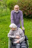 Old lady with dementia in a wheelchair and carer royalty free stock images