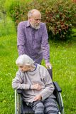 Old lady with dementia in a wheelchair and carer stock image