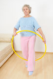 Old lady doing gymnastic with hula-hoop Royalty Free Stock Photos