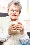 Old lady drinking a brew of herbs Stock Photography