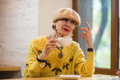 Old lady drinking coffee. Royalty Free Stock Images