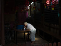 An old lady eats supper in a beam of light. An old lady living on the Chew Jetty eats supper in a beam of light Royalty Free Stock Photos