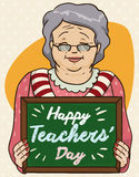 Old Lady Educator Celebrating Teachers. Cute smiling old lady educator holding a little chalkboard gift from her students in Teachers Day celebration Royalty Free Stock Photo