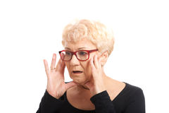 An old lady expresses shock/ surprise. Isolated on white stock image