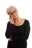 An old lady in eyeglasses touches her face. Royalty Free Stock Images