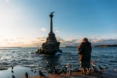 Old lady feed gulls near Sevastopol symbol - Monument to the Sunken Ships, Famous historical architecture of Crimea peninsula royalty free stock photos