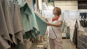 Old lady is feeling and checking towel in a shop, in a trading area. Female shopper is touching soft cloth in trading area in big store. She is doing shopping stock video footage