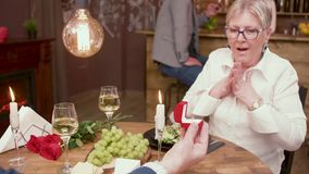 Old lady gets marriage proposal on a romantic date. Old man offering an engagement ring to his date stock footage