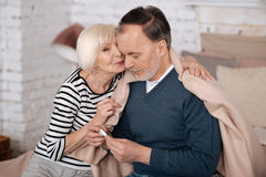 Old lady giving solace to her sick husband. So cute. Pleasant senior women is kissing her sick husband sitting covered with blanket near her Stock Images