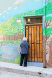 Old lady and graffiti. VALPARAISO - NOVEMBER 07: People in front of coffee shop on the streets of colourful districts of the protected UNESCO World Heritage Site royalty free stock image