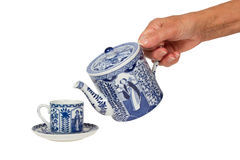Old lady (hand) with an antique Dutch teapot and cup in Delfts b stock photo