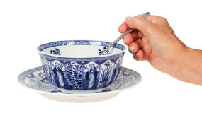Old lady (hand) holding a spoon in an antique Dutch soup bowl in Stock Images