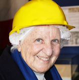 Old lady with a hard hat. Portrait of an old lady wearing a net and a hard construction hat just before taking a tour of war shelters for safety Royalty Free Stock Photography