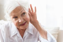 Old lady is having difficulty with auditory perception. Repeat, please. Close-up of face of charming elderly woman is holding hand by her ear and struggling to royalty free stock images