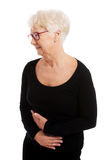 An old lady is having a stomachache. Stock Images