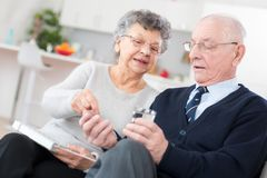 Old lady helping husband to take right pills Stock Photo