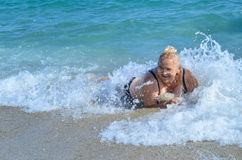 Old lady hit by wave in sea. Old lady enjoying sea waves Royalty Free Stock Images