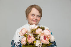 Old lady holding bouquet of flowers in hand Stock Image